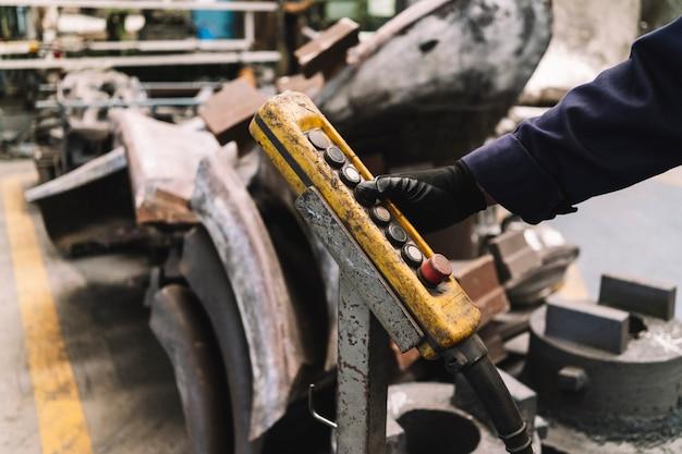 Detail van de hand van een man die een commando van een industriële kraan bedient in een metaalsmelterij