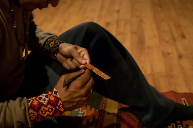 Detail van de handen van de sjamaan terwijl hij de kambãƒâƒã'â² voorbereidt: een stof die wordt gewonnen uit de klieren van een zuid-amerikaanse kikker voor zijn sjamanistische ceremonie