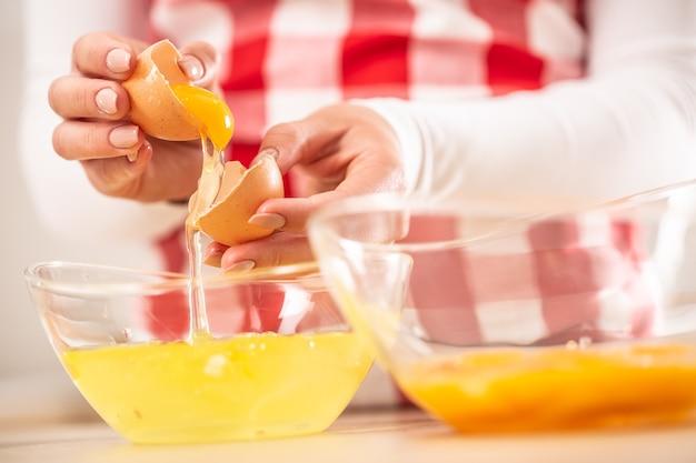Detail van de handen van de vrouw die eierdooiers van het wit scheiden in twee glazen kommen.