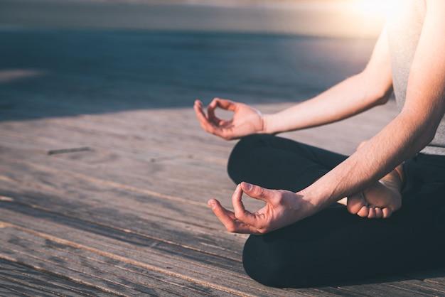 Detail van de handen van een jonge man die mediteert bij het beoefenen van yoga op enkele houten planken in de lotuspositie.
