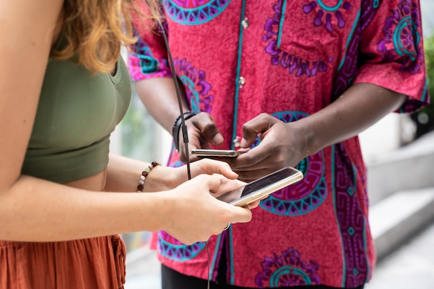 Detail van de handen van een multiraciale groep samen op straat met mobiele telefoons