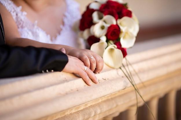 Detail van de handen van een paar met trouwringen