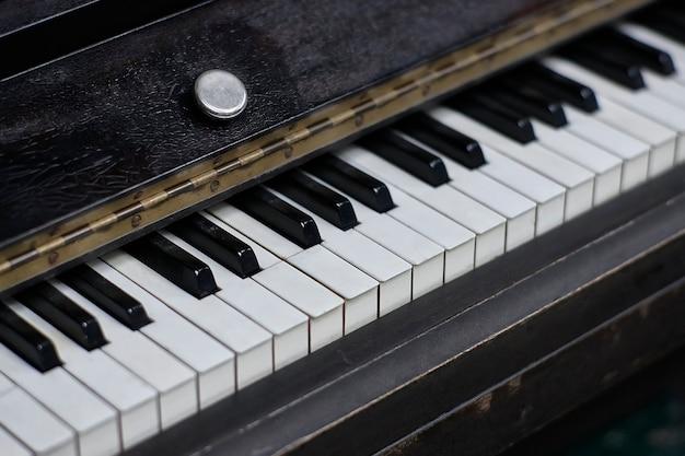 Detail van de ivoren toetsen en het frame van een antieke luxe piano bedekt met leer.