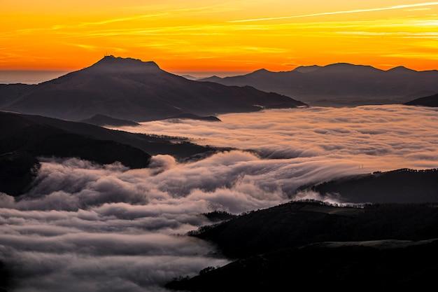 Detail van de prachtige berg larrun op een winterochtend aan de zee van wolken op het gouden uur van de dageraad. baskenland