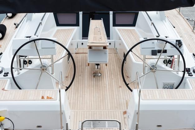 Detail van de stuurwielen en symmetrie in het dek van een luxe zeiljacht.