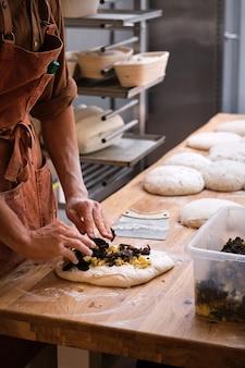 Detail van een bakkershand die ingrediënten in het brooddeeg introduceert
