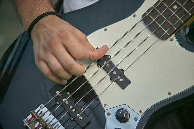 Detail van een bassist die zijn eacoustica bas speelt tijdens een live rockmuziekconcert.