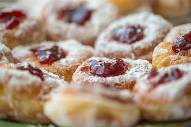 Detail van een bord donuts gevuld met jam en bedekt met suiker.