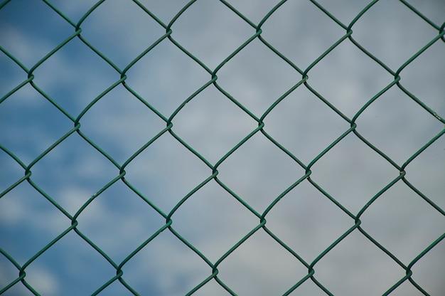 Detail van een draadgaas met macro-opname en op de achtergrond het blauw van de lucht, ideaal als textuur en als een gevoel van verlangen naar vrijheid.