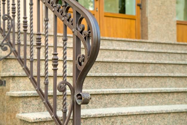 Detail van een gevel. nieuwe granieten trap met metalen leuningen.