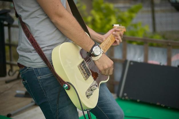 Detail van een gitarist die zijn elektrische gitaar speelt tijdens een live rockmuziekconcert.