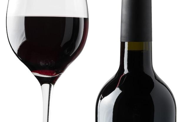 Detail van een glas rode wijn naast een fles op een zwarte achtergrond