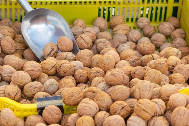 Detail van een groep natuurlijke walnoten die in bulk op een straatmarkt worden verkocht
