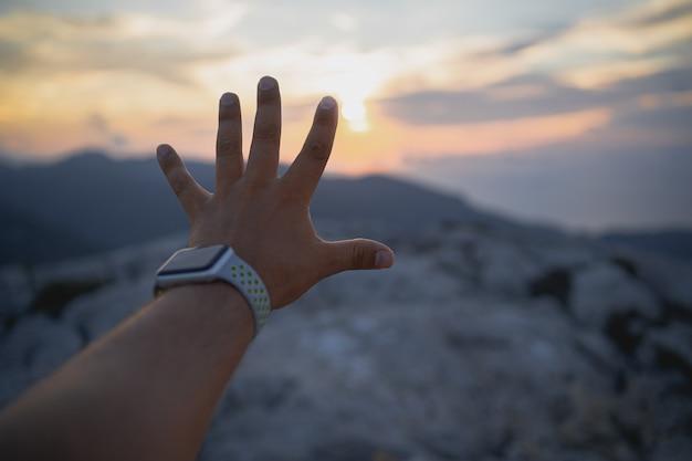 Detail van een hand die de zon probeert te vangen tijdens een zonsondergang