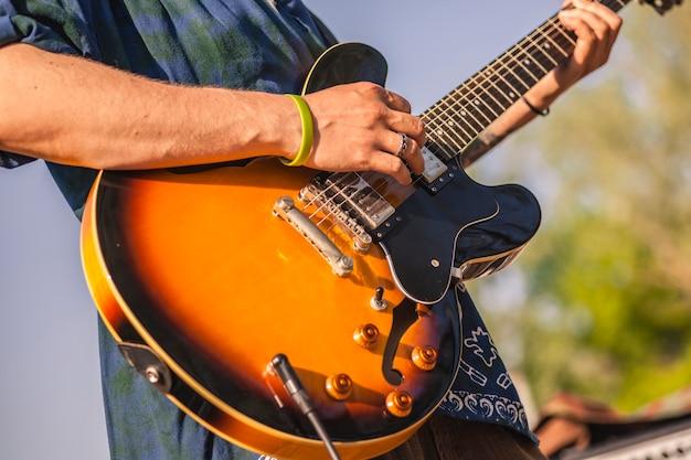 Detail van een kleurrijke elektrische gitaar die wordt vastgehouden door een muzikant die erop speelt