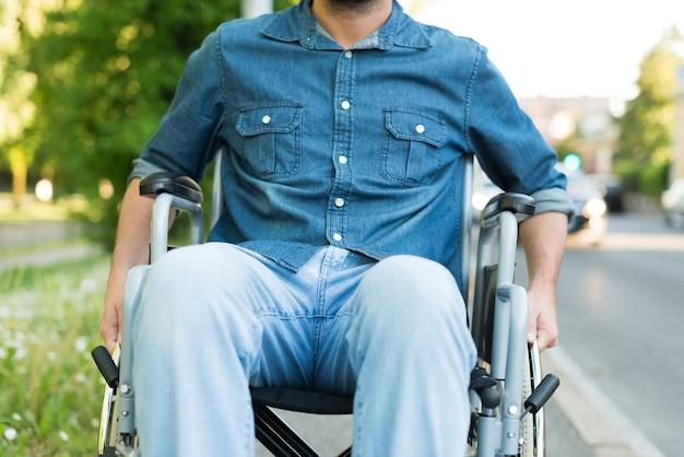 Detail van een man met behulp van een rolstoel in een stedelijke straat