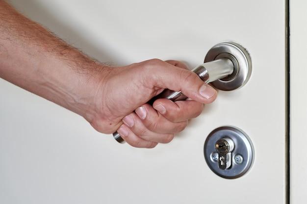 Detail van een mannenhand die een deur opent