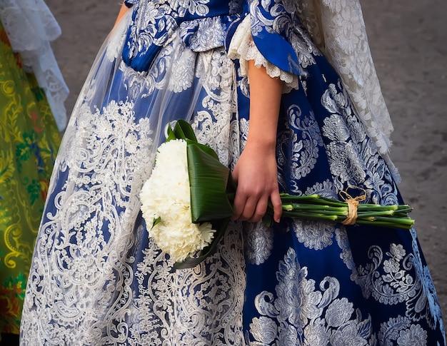 Detail van een met de hand geborduurd faller-kostuum en een boeket bloemen in las fallas, valencia, spanje