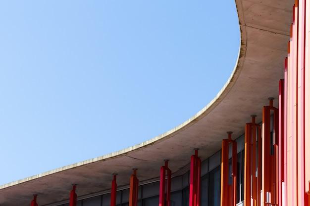 Detail van een modern architectuurgebouw met blauwe hemel op de achtergrond.