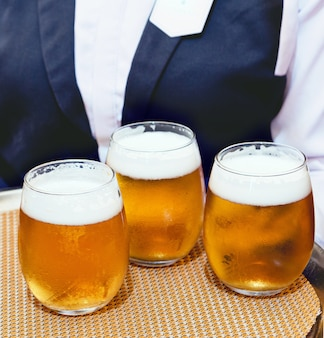 Detail van een ober in pak koud ambachtelijk bier serveren op een dienblad tijdens een feest in een restaurant