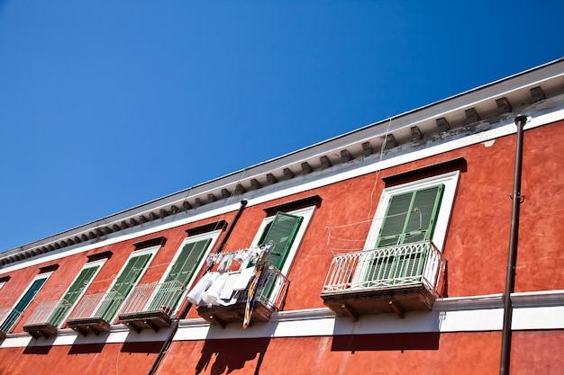 Detail van een oud rood huis met een blauwe hemelachtergrond in procida isle, italië