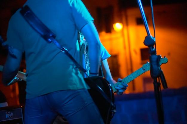 Detail van een rockmuzikant die de bas live speelt tijdens een concert met rook en zachte lichten. artistieke foto met de gefilterde opname van de lichten.