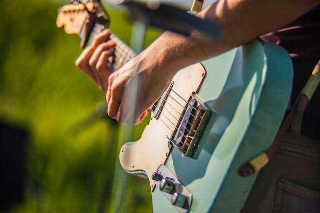 Detail van een rockmuzikant die een elektrische gitaar speelt