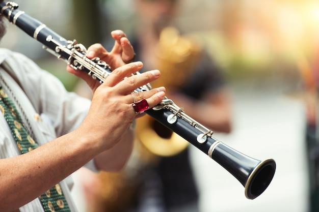 Detail van een straatmuzikant die de klarinet speelt