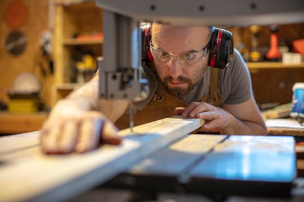 Detail van een timmerman gericht op het snijden van een stuk hout met precisie