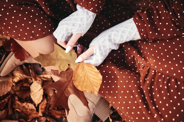 Detail van een vrouw die zit met een bos herfstbladeren