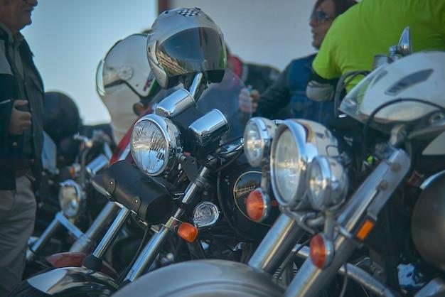 Detail van een vuurtoren van een aangepaste motorfiets geparkeerd in het midden van andere fietsen.