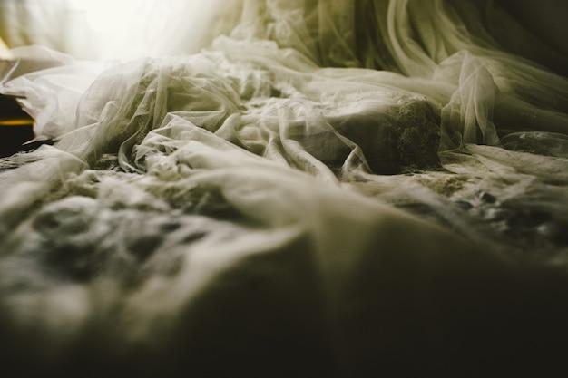 Detail van een witte en elegante trouwjurk.
