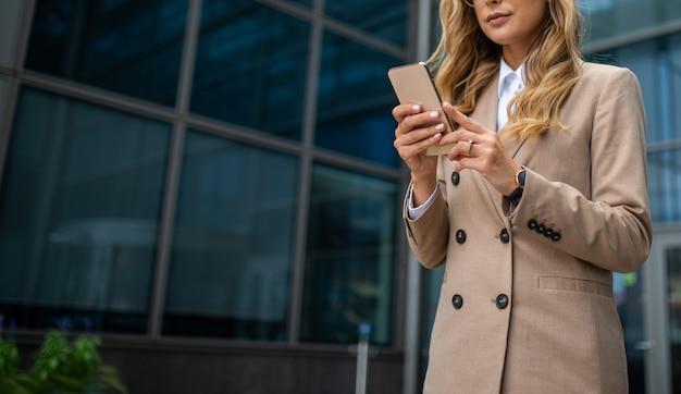 Detail van een zakenvrouw die haar mobiele telefoon gebruikt