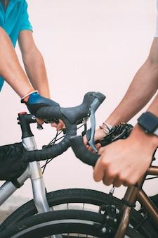 Detail van fietsers die fietsen berijden handen van twee fietsers die het stuur van een fiets vasthouden copy spacevertical