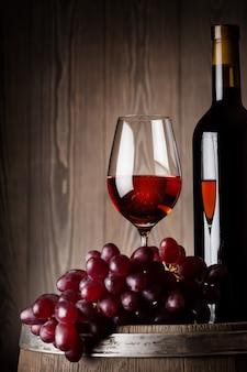 Detail van fles en glas rode wijn met druiven