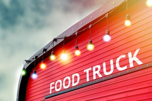 Detail van gesloten rode voedselvrachtwagen met gloeilampenachtergrond, geen mensen