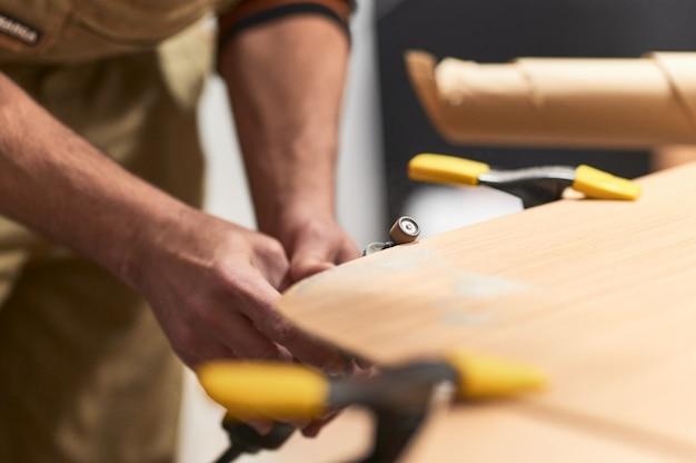 Detail van handen die de rand van een houten plank gladstrijken met een dremel-machine.