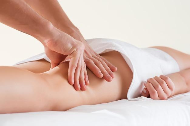 Detail van handen die menselijke kuitspier masseren. therapeut die druk uitoefenen op vrouwelijk been.