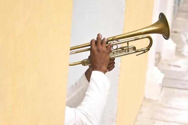 Detail van handen van cubaanse muzikant trompet spelen in kleurrijke straat van havana, cuba