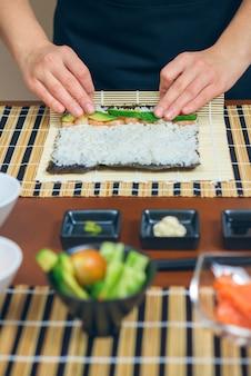 Detail van handen van vrouwelijke chef-kok die japanse sushi oprolt met rijst, avocado en garnalen op nori-zeewierblad