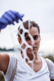 Detail van het gezicht van een meisje dat ons een stuk plastic in haar hand laat zien