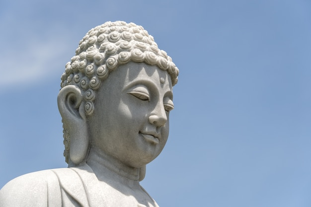 Detail van het hoofd marmeren standbeeld van boedha in een boeddhistische tempel en een blauwe hemel