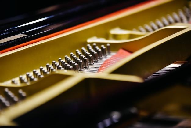 Detail van het interieur van een piano met het klankbord, snaren en pinnen.