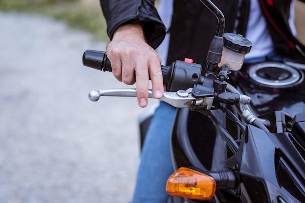 Detail van het stuur van een motorfiets met de rem en de hand van de piloot