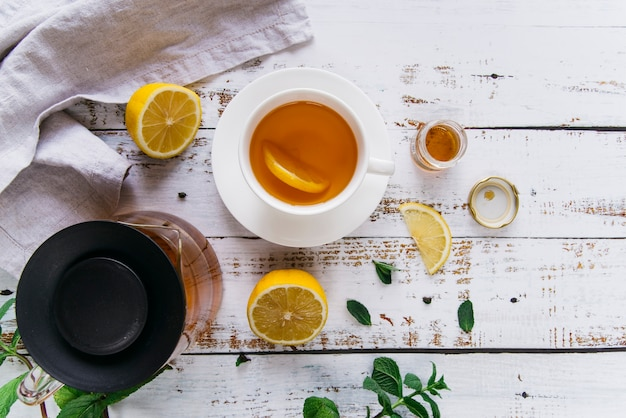 Detail van kop thee met citroen en verse munt op witte houten lijst