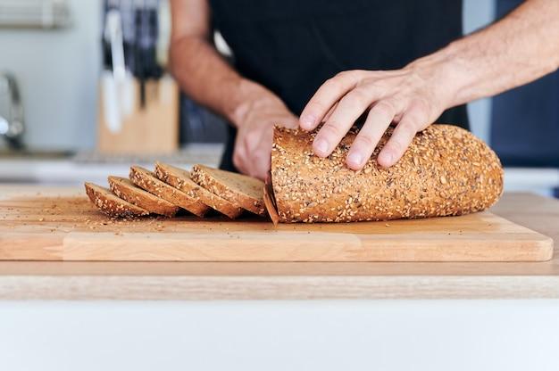 Detail van mannenhanden die sneetjes volkorenbrood met zaden snijden