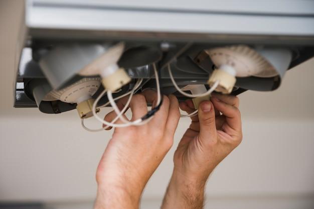 Detail van menselijke hand wordt geschoten die plafondlichten herstellen die