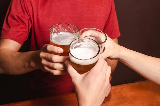 Detail van mensen die hun glazen met bier rammelen, aan de bar.