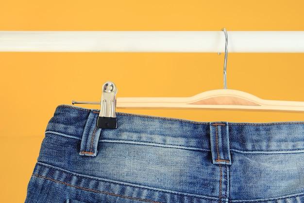 Detail van opgehangen blauwe spijkerbroek met gele achtergrond