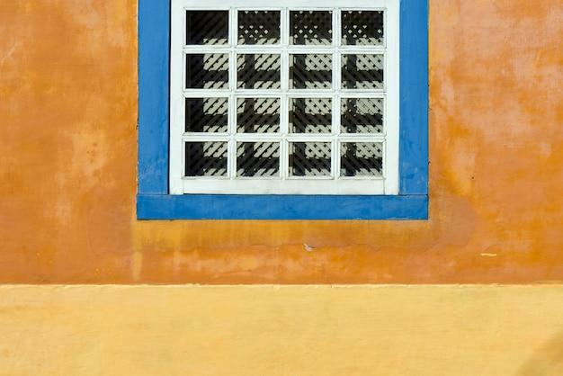 Detail van oude venster in gele muur